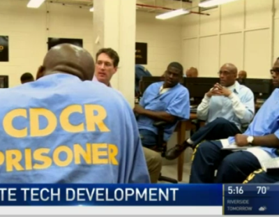Screenshot of news story about inmate tech development showing several students and mentor looking off into the distance.