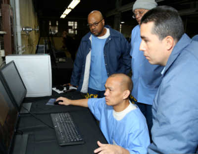 Four San Quentin students surrounding a computer looking at code intently.