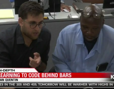 Screenshot of KRON4 broadcast featuring TLM student and mentor looking at code.