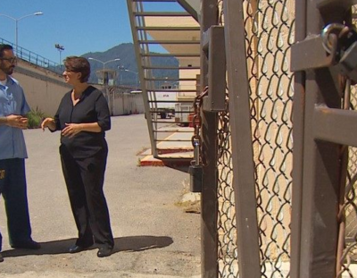 Tommy Winfrey talking to a woman in San Quentin next to padlocked gate.