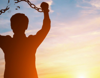 Shackled man holding his arms up and breaking his chains in front of a sunset.