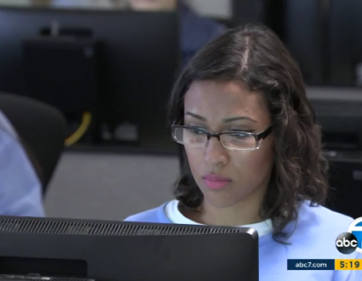 Screenshot of an ABC 7 news story showing a female student wearing glasses looking at her monitor.