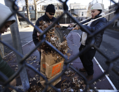 Three people cleaning leaves off a basketball court behind a chain link fence.